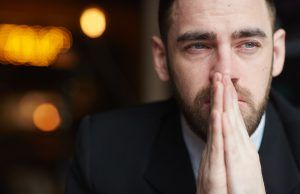 como explicar a los niños el coronavirus, Portrait of modern bearded businessman looking away with red teary eyes, stressed and tired against black background, covering his mouth with hands