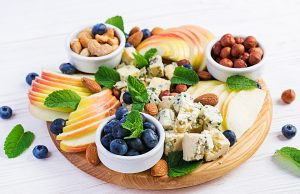 Cheese platter with assorted cheeses, blueberry, apples, nuts on white table. Italian cheese platter and fruit.