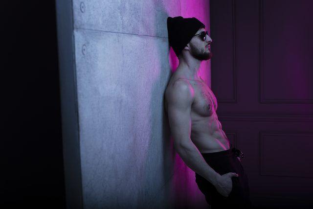 ess fit brutal young man in hat posing in dark studio with wall with purple neon complementary color, Rutina abdomen para oblicuos y abdomen bajo | TABATA en tiempo real 4 minute workout